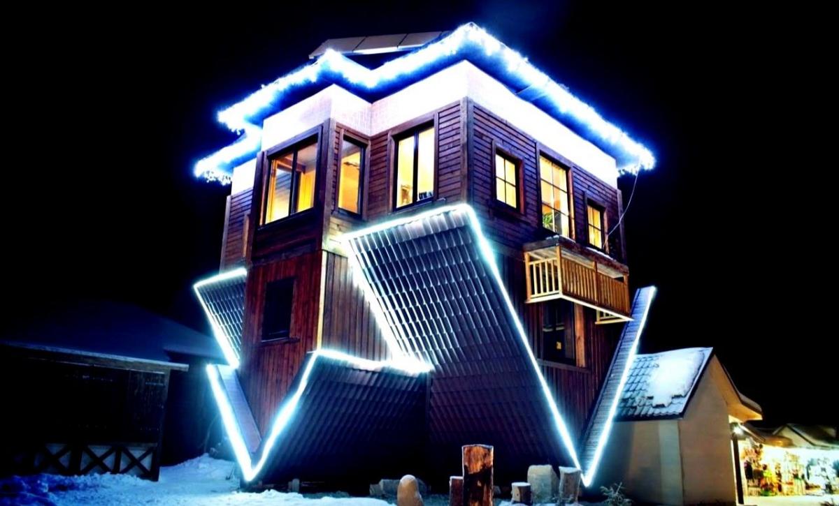 Перевернутий будинок вночі з освітленням
